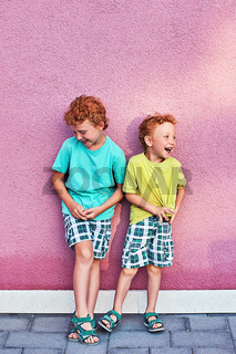 Two cute red curly boys brothers are having fun laughing on the pink wall background