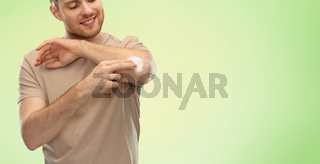 young man applying pain medication to his elbow