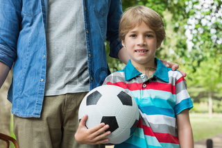 Portrait of a boy holding football besides his father