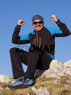 Bergsteiger in Siegerpose auf einem Felsen