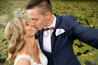 Wedding selfie. Bride and groom kissing passionately outdooors in park.