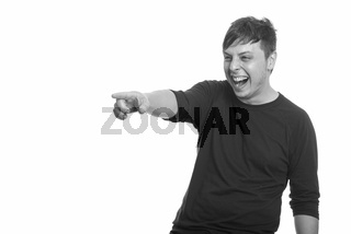 Studio shot of Caucasian man laughing and pointing finger
