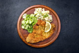 Traditional deep-fried schnitzel with potato and cucumber salad offered as top view on a rustic wooden board with copy space