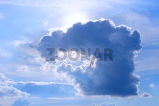 sun peeking out from behind dark cloud