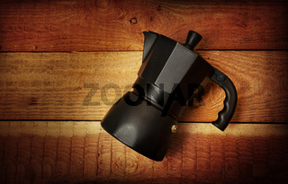 Black Italian coffee maker isolated on wooden background