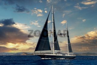 Two-masted yacht in the Mediterranean sea at sunset