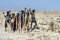 Afar salt workers breaking salt blocks from the salt crust of Lake Assale, Ethiopia