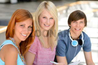 Three smiling student friends looking at camera
