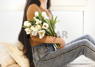 Happy woman with flowers sitting on windowsill