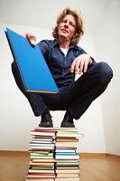 Mann auf Bücherstapel schenkt Buch