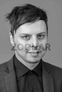 Face of happy businessman wearing suit in black and white