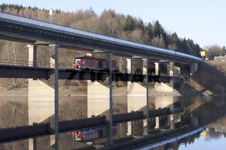 Ein Zug fährt unter einer Brücke durch