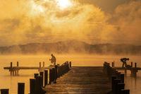 Bathing during sunrise at lake Woerthsee, Bavaria, Germany