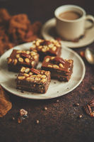 Chocolate cake with caramel frosting, pecans and hot coffee, on rustic background. Freshly baked