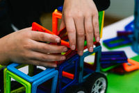 The child collects a toy car from the designer. Engineering constructions in miniature. The development of motor skills of hands, thinking, memory and imagination in a child.