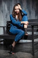 Cute young woman dressed in denim overalls