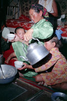 In the yurt of a Mongolian family in Gobi desert: Mother pours butter tea in a bowl - photo 1977