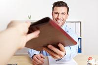 Bewerber überreicht Bewerbungsunterlagen
