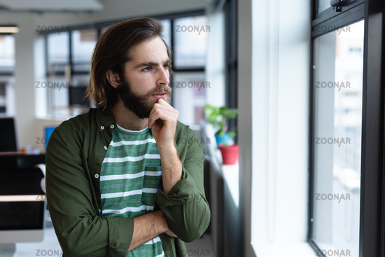 Caucasian businessman in thought looking through window in creative office