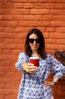 Portrait of a young beautiful woman holding a plastic red glass with coffee in front of her.