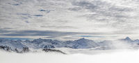 Snow covered mountains with inversion valley fog and trees shrouded in mist. Panoramic snowy winter landscape in Alps, Allgau, Kleinwalsertal, Bavaria, Germany.