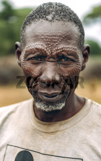 TOPOSA TRIBE, SOUTH SUDAN - MARCH 12, 2020: Elderly male in dirty t shirt and with traditional scars on face looking at camera while living in Toposa Tribe village in South Sudan, Africa