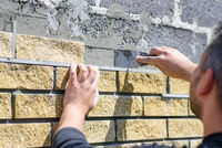 Man decorates the facade of the fence with decorative torn bricks, close up. Work near home