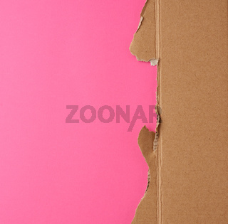 torn edges of corrugated brown cardboard paper on a pink background