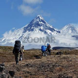 Group of tourists and travelers climbing to mountains on background of volcanoes