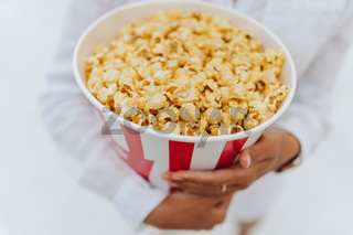 Close-up photo of a young sweet girl, who is holding a tube of popcorn in her hands.