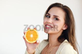 Young girl holding ripe orange isolated on light background