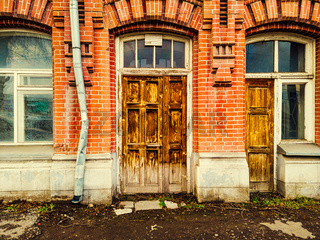 Closed wooden door of the entrance to the old brick building