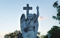 Stone angel statue with a silence sign and pointing up to heaven at the cemetery, Merida, Mexico