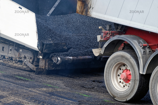 paver was loaded by a dump truck