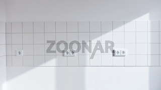 Weiße Wand mit Fliesen und Steckdose in leerer Küche
