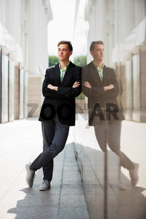 Young fashion man standing against the wall
