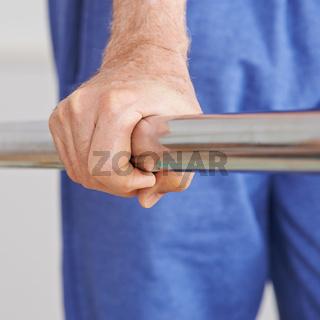 Hand hält sich am Geländer fest