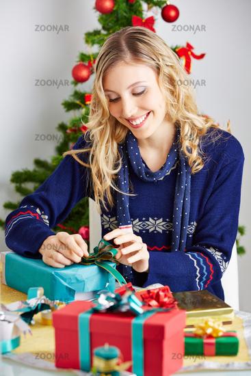 Frau klebt Schleife auf Geschenk zu Weihnachten