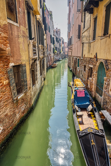 Small canal with traditional gondola seen in Venice, Italy