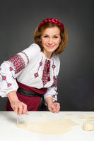 Adult woman in traditional ukrainian style. Cooking ukrainian varenyky with cherries. Serie.