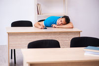 Exhausted male student preparing for the exams in the classroom