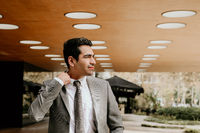 Handsome businessman walking outdoors with office building in the background.