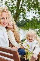 Familie sitzt im Herbst auf Bank