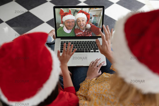 Rear view of woman and daughter in santa hats waving while having a videocall with senior couple in
