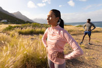 Fit african american couple in sportswear standing in tall grass