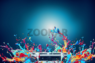 Abstract colorful paint splash with vintage stereo cassette player over blue background