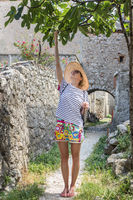 Beautiful blonde young female traveler wearing straw sun hat enjoying summer on Mediterranean cost, picking fruits under a fig tree with lavander flowers and traditional old stone house in background