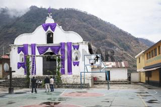 Local men decorating the church with purple cloth for easter in the mountain village Santa Cruz la Laguna, Guatemala