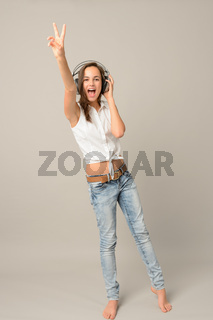 Singing teenage girl headphones show victory sign