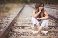 Sad young woman sitting on the railway.